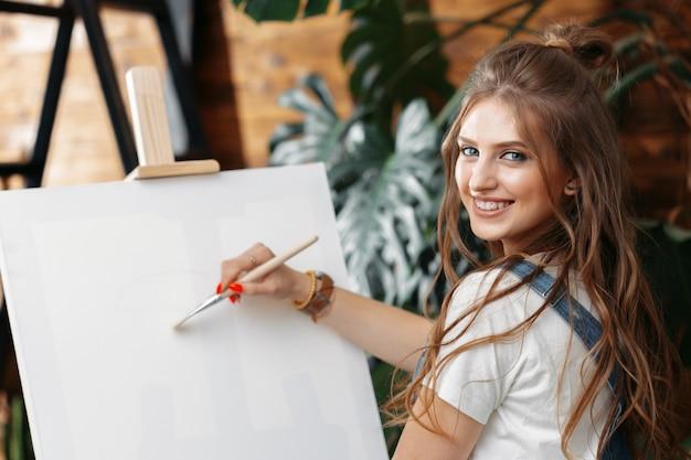 Vrij getalenteerde vrouwelijke schilder die op schildersezel schildert Premium Foto