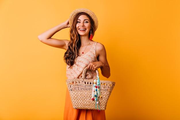 Vrij glamoureus meisje wat betreft haar strooien hoed. studio portret van vrolijke jonge vrouw met zomer tas. Gratis Foto