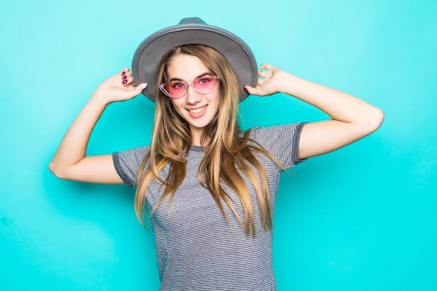 Vrij glimlachend jong model in maniert-shirt, hoed en transparante bril die op groene achtergrond wordt geïsoleerd Gratis Foto