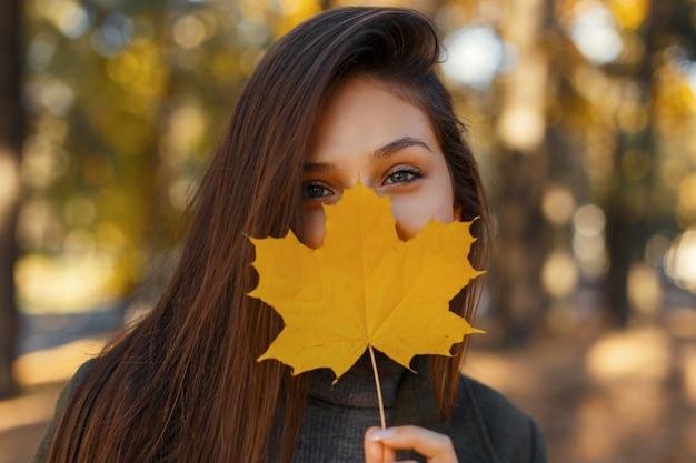 Vrij jong gelukkig meisje met een glimlach bedekt haar gezicht met een goudgeel herfstblad op de natuur Premium Foto