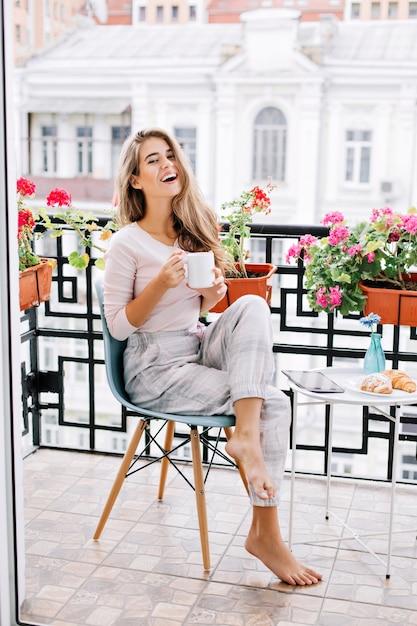Vrij jong meisje met lang haar dat 's ochtends op balkon ontbijten. ze houdt een kopje vast en glimlacht. Gratis Foto
