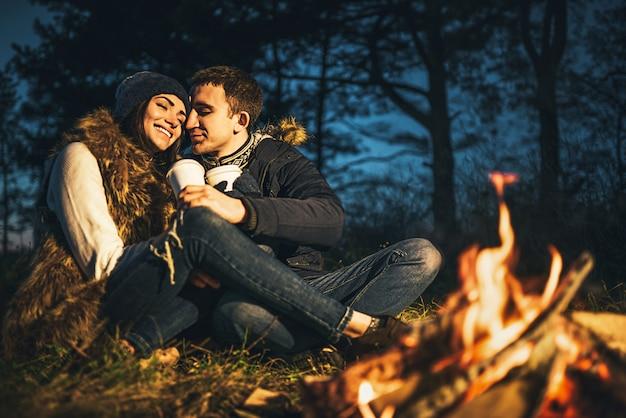 Vrij jong paar dat hete drank in het bos drinkt dichtbij vuur. Premium Foto