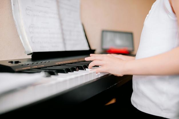 Vrij jonge musicus die klassieke digitale piano thuis speelt tijdens online klasse thuis Premium Foto