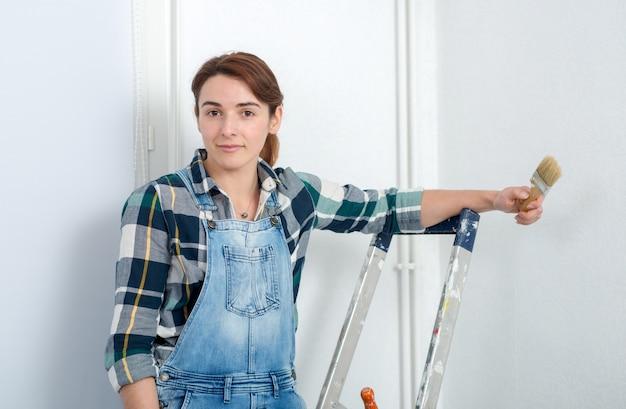 Vrij jonge vrouw die de muur schildert Premium Foto