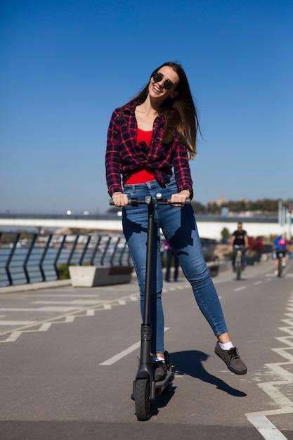 Vrij jonge vrouw die een elektrische autoped in de straat berijdt Premium Foto
