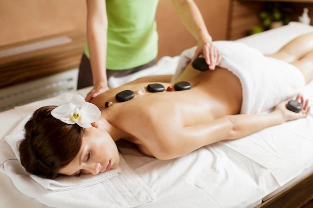 Vrij jonge vrouw die een hete therapie van de steenmassage heeft Premium Foto