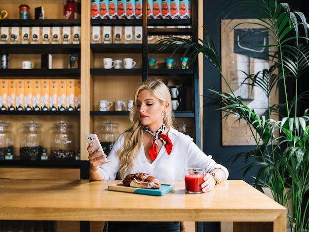 Vrij jonge vrouw die het mobiele glas van de telefoonholding van sap in cafã� met behulp van Gratis Foto