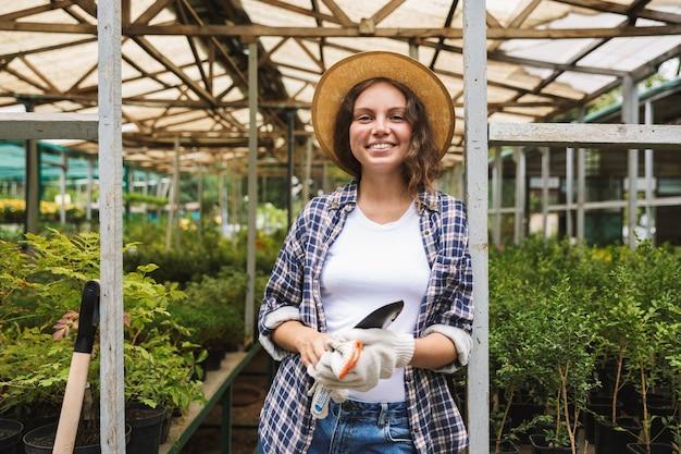 Vrij jonge vrouw die in een serre werkt Premium Foto
