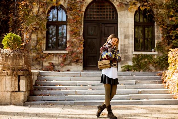 Vrij jonge vrouw die in het de herfstpark loopt Premium Foto