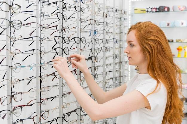 Vrij jonge vrouw die in opticaopslag oogglazen kiest Gratis Foto
