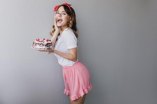 Vrij jonge vrouw die in roze rok verjaardag viert. enthousiast donkerharig meisje dat met zoete cake danst. Gratis Foto