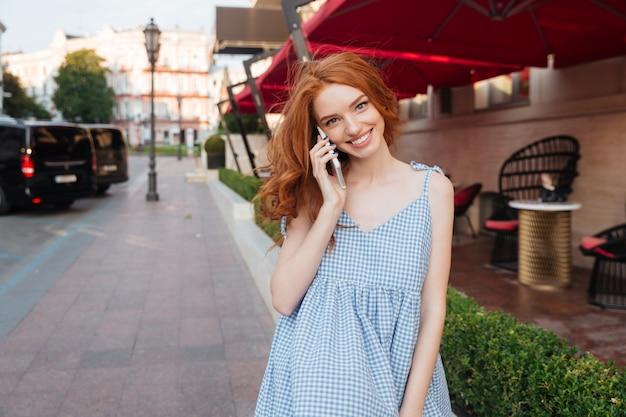 Vrij jonge vrouw die met lang haar op mobiele telefoon spreekt Premium Foto