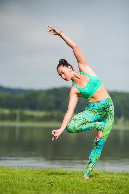 Vrij jonge vrouw die yogaoefeningen in het park doet Gratis Foto