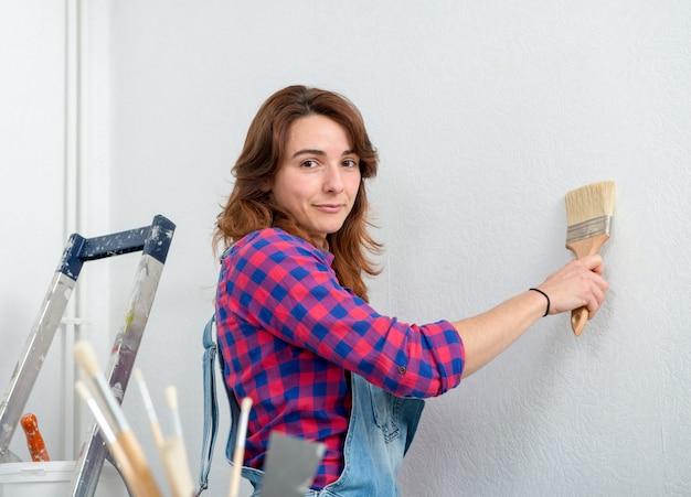 Vrij jonge vrouw het schilderen muur witte kleur Premium Foto