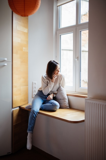 Vrij jonge vrouwenzitting op windowhill in jeans en witte t-shirt Gratis Foto