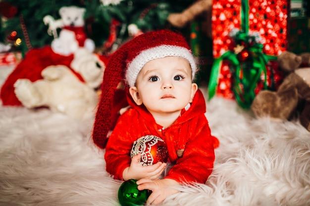 Vrij kleine jongen in rood kostuum vóór een kerstboom Premium Foto