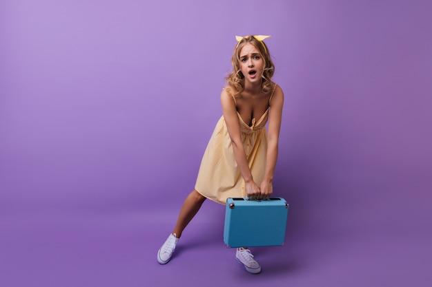 Vrij krullend meisje poseren met zware koffer. de europese vrouw die van debonair haar valise op violet houdt. Gratis Foto
