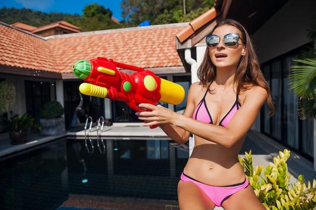 Vrij lachende gelukkige vrouw spelen met watergun speelgoed bij zwembad op tropische zomervakantie op villahotel plezier in bikini zwembroek, kleurrijke stijl, feeststemming Gratis Foto