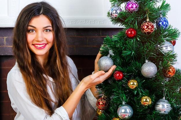 Vrij lachende meisje met lichte make-up en geweldige brunette lange haren versiert de kerstboom. Gratis Foto