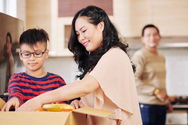 Vrij lachende volwassen vrouw en haar zoon die verse groenten en fruit uit de kartonnen doos nemen Premium Foto