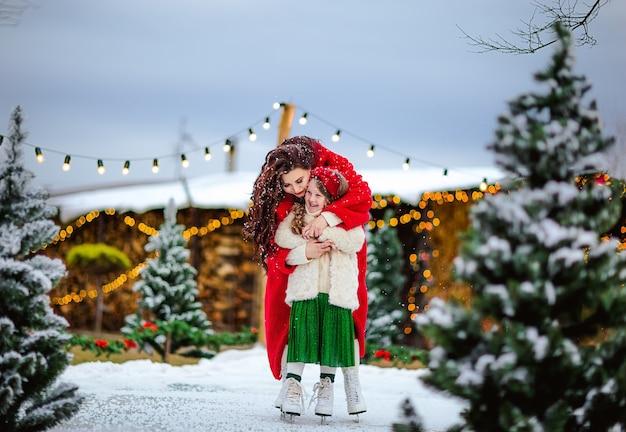 Vrij langharige meisje en mooie brunette vrouw schaatsen op de open ijsbaan. kerst achtergrond. Premium Foto