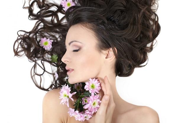 Vrij mooi meisje dat met heldere bloemen in haar haar heldere make-up ligt die op wit wordt geïsoleerd Gratis Foto