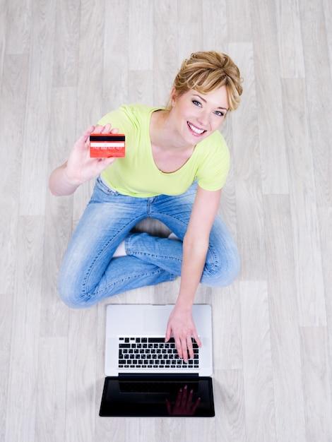 Vrij mooie jonge vrouw zittend op de vloer met creditcard en met behulp van laptop Gratis Foto