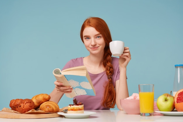 Vrij mooie roodharige vrouw heeft een goed gezond ontbijt, met een aangename glimlach op zoek naar voren, drinkend leesboek Gratis Foto
