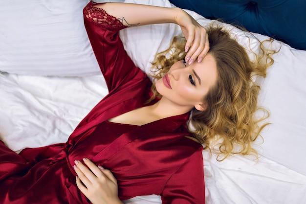 Vrij sensueel blond model liggend op het bed, geniet van haar ochtend in een luxehotel, gekleed in bordeauxrood zijden nachthemd en gewaad, blinde haren en schoonheidsgezicht, boudoir-stijl. Gratis Foto