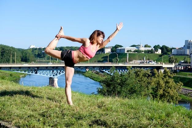 Vrij slanke vrouw beoefenen van yoga buitenshuis Premium Foto