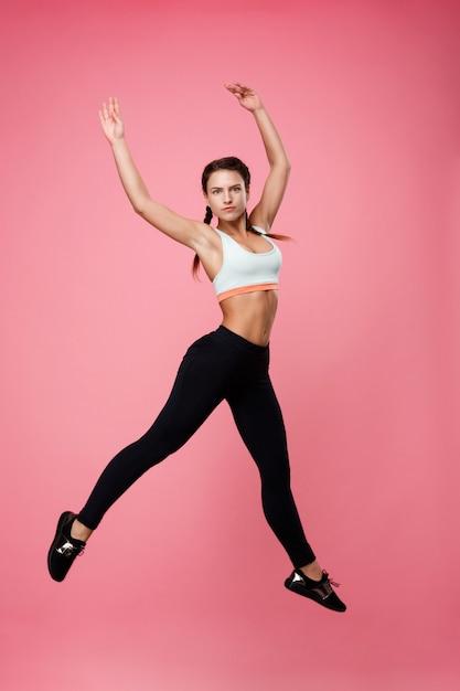 Vrij sportieve vrouw in bovenkant en leggins die als ballerina springen Gratis Foto