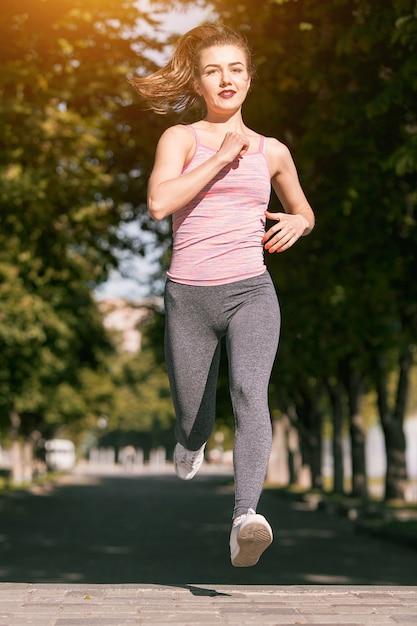 Vrij sportieve vrouwenjogging bij park in zonsopganglicht Gratis Foto