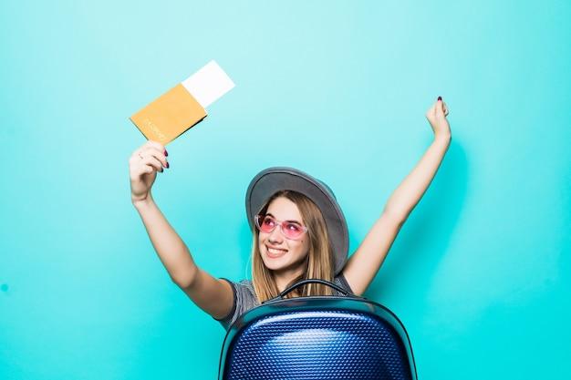 Vrij tienermeisje houdt haar paspoortdocumenten met kaartje in haar handen en blauwe koffer die op groene studiomuur wordt geïsoleerd Gratis Foto