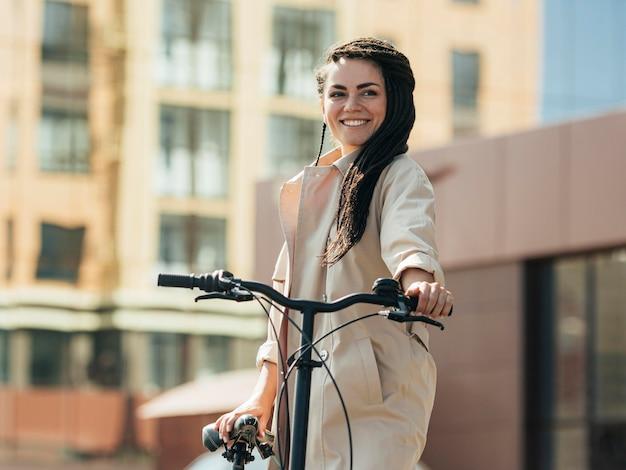 Vrij volwassen vrouw poseren met milieuvriendelijke fiets Premium Foto
