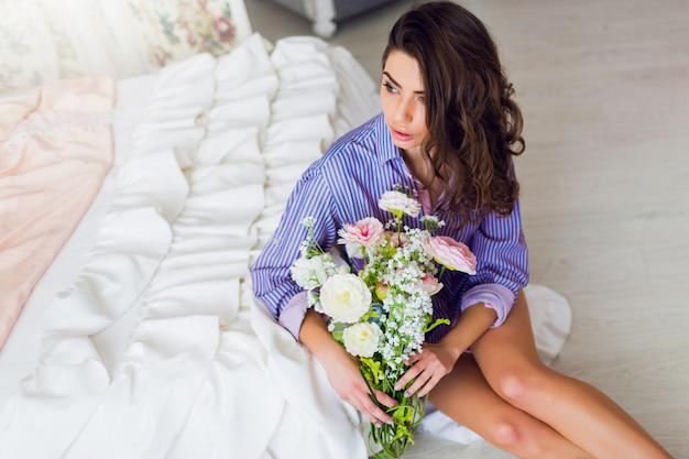 Vrij vrolijke brunette vrouw in gestreepte t-shirt zittend op de vloer met lentebloemen in handen Gratis Foto