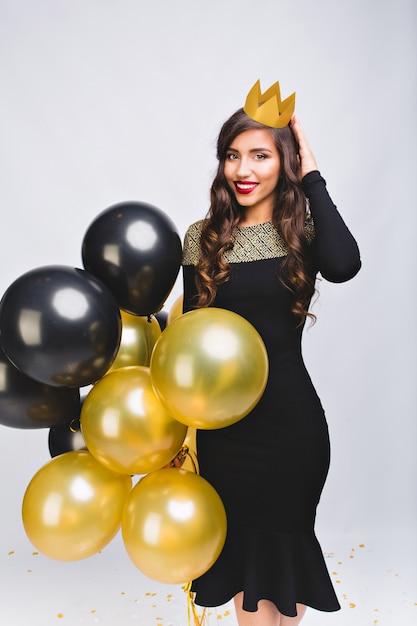 Vrij vrolijke stijlvolle vrouw in zwarte luxe avondjurk en gele kroon op hoofd glimlachend en met gele en zwarte ballonnen. Gratis Foto