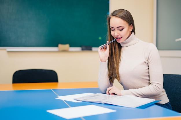 Vrij vrouwelijke schoolleraar die in bureau werkt Premium Foto