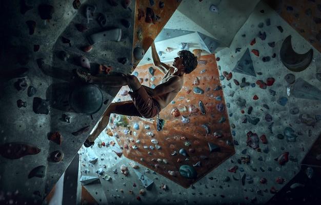 Vrije klimmer jonge mens die kunstmatige kei binnen beklimt Gratis Foto