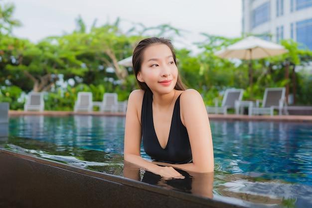 Vrije tijd van de portret ontspant de mooie jonge aziatische vrouw glimlach rond openluchtzwembad voor vakantie Gratis Foto