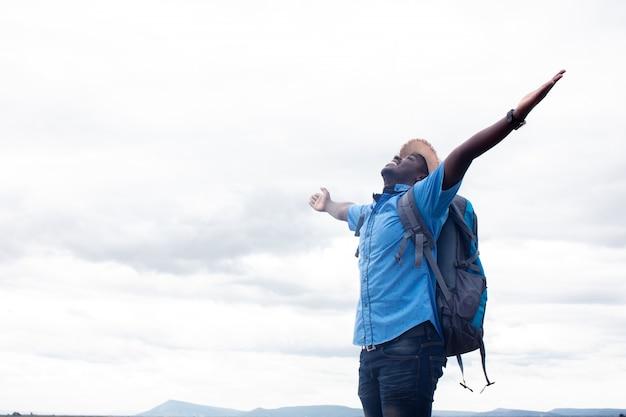 Vrijheid afrikaanse toeristische reiziger man met rugzak op uitzicht op berg Premium Foto