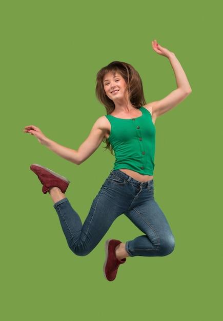 Vrijheid in beweging. in de lucht schot van vrij gelukkige jonge vrouw die en tegen oranje studioachtergrond springt gebaren. Gratis Foto
