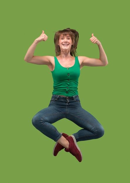 Vrijheid in beweging. in de lucht schot van vrij gelukkige jonge vrouw springen en gebaren op groen Gratis Foto
