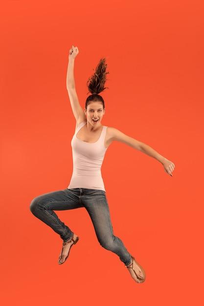 Vrijheid in beweging. in de lucht schot van vrij gelukkige jonge vrouw springen en gebaren tegen oranje studio achtergrond. menselijke emoties en gezichtsuitdrukkingen concept Gratis Foto