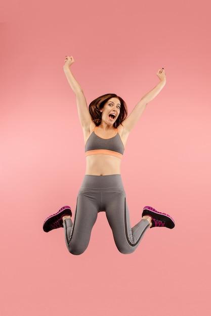 Vrijheid in beweging. in de lucht schot van vrij gelukkige jonge vrouw springen en gebaren tegen oranje studio achtergrond. runnin meisje in beweging of beweging. menselijke emoties en gezichtsuitdrukkingen concept Gratis Foto