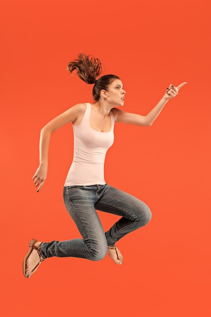 Vrijheid in beweging. in de lucht schot van vrij gelukkige jonge vrouw springen en gebaren tegen oranje studio. Gratis Foto