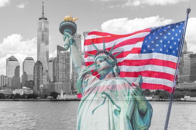 Vrijheidsbeeld met een grote amerikaanse vlag en de skyline van new york in de Premium Foto
