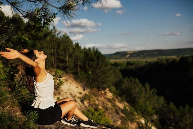 Vrijheidsmeisje met handen omhoog in de bergen. ze voelt zich sterk en zelfverzekerd. Premium Foto