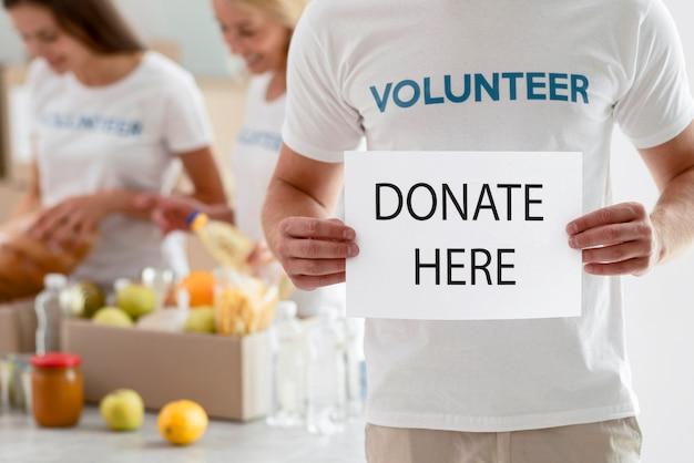 Vrijwilliger met aanplakbiljet met instructies voor donatie Gratis Foto