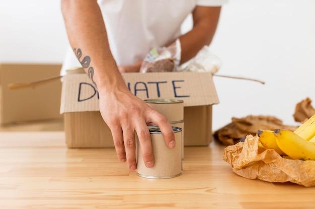 Vrijwilliger plaatsen van blikjes met voedsel in dozen close-up Gratis Foto