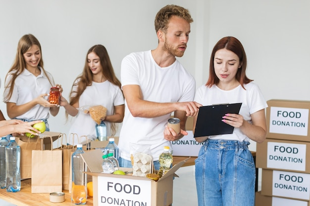 Vrijwilligers brengen voedsel in dozen voor donaties Gratis Foto